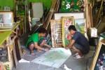 Dua pegawai Toko Kerajinan Gria Pigura di Jl. Museum Sriwedari No. 29, Solo mengerjakan pemasangan pigura, awal pekan lalu. (Muhammad Reza Santirta/JIBI/Solopos)
