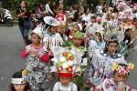 Peserta Karnaval Sebelas melintas di jalan perkampungan RW 011 Gremet, Manahan, Banjarsari, Solo, Jawa Tengah, dengan mengenakan busana yang dibuat dari koran bekas, Minggu (24/8/2014). (Ardiansyah Indra Kumala/JIBI/Solopos)