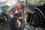 Seorang petugas keamanan mengotong seorang lelaki bersimbah darah yang diduga sebagai salah seorang pendukung pasangan capres dan cawapres Prabowo Subianto dan Hatta Rajasa. Lelaki itu, menurut Kantor Berita Antara, cedera saat berorasi di silang Monas, Bundaran HI, Jakarta, Kamis (21/8/2014). (JIBI/Solopos/AntaraOscar Motuloh)