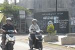 Pengendara sepeda motor melintasi sebuah graffiti Islamic State of Iraq and Syiria (ISIS) di salah satu persimpangan jalan di kompleks pabrik cat Avian di Dukuh Cemani, Desa Cemani, Grogol, Sukoharjo, Senin (4/8). Graffiti itu bahkan sudah terlihat sejak sebulan terakhir. (Aries Susanto/JIBI/Solopos)