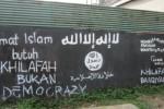 Graffiti bertuliskan dukungan untuk kelompok ekstremis Islamic State of Iraq and Syria (ISIS) terpampang di tembok toko sebelum Pasar Karangpandan, Karanganyar, jawa Tengah, Minggu (3/8/2014). Graffiti serupa juga tampak di sepanjang jalur jalan Solo-Tawangmangu hingga jalan tembus Cemoro Sewu-Sarangan, Jawa Timur.