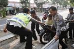 Polisi Lalu Lintas menaikkan sepeda motor Honda Supra X berpelat nomor AD 6159 JD yang dikendarai Sri Asriyah, 44, ke mobil pikap dinas mereka. Sri Asriyah adalah korban kecelakaan lalu lintas di Jl. Adisucipto, Paulan, Colomadu, Karanganyar, Kamis (14/8/2014). (Septian Ade Mahendra/JIBI/Solopos)