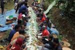 Sejumlah warga menyantap makanan bersama di pinggir Sungai Dawuhan saat ritual Nyadran 1.000 Kupat di Dusun Gedongan, Ngemplak, Kandangan, Temanggung, Jawa Tengah, Jumat (29/8/2014). Ritual Nyadran 1.000 Kupat yang rutin dilaksanakan setiap tahun pada hari Jumat Kliwon bulan Syawal tersebut merupakan wujud penghormatan warga kepada mendiang Simbah Kiai Lenging, tokoh adat pendiri dusun. Ritual itu sekaligus wujud rasa syukur warga seusai panen kopi. (JIBI/Solopos/Antara/Anis Efizudin)