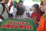 Pengunjung Waduk Gajah Mungkur, Sendang, Wonogiri mencicipi olahan pangan lokal nugget jambu mete yang diikutkan Festival Pangan Lokal di Kompleks Objek Wisata WGM, Senin (4/8/2014). (Trianto HS/JIBI.Solopos)