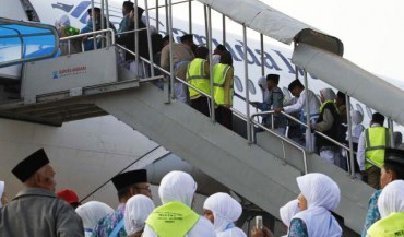 Jemaah calon haji kelompok terbang pertama di Embarkasi Solo yang berasal dari Brebes, Jawa Tengah menaiki tangga pesawat di Bandara Adi Soemarmo, Solo, di Ngemplak, Boyolali, Senin (1/9/2014). Sebanyak 363 calon haji kloter pertama itu diterbangkan menuju Jedah, Arab Saudi dengan pesawat bernomor penerbangan GA-600. (Septian Ade Mahendra/JIBI/Solopos)