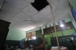 Guru membaca buku di bawah langit-langit yang nyaris roboh di SDN Nayu Barat 2 Solo, Senin (15/9/2014). Langit-langit ruang kelas tempat kegiatan belajar tersebut dibiarkan rusak dan belum diperbaiki sejak 2012 silam. (Septian Ade Mahendra/JIBI/Solopos)