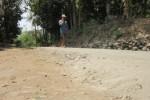 Seorang warga berjalan kaki di ruas jalan yang diprotes warga lantaran tak sesuai standard betonisasi, Minggu (7/9/2014). Jika dilintasi kendaraan, bahan materil mengelupas dan debunya berterbangan menuju rumah warga. (Mariyana Ricku/JIBI/Solopos)