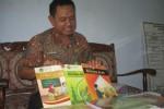 Kasi Madrasah Kementerian Agama Wonogiri, Achmad Farid, menunjukkan tiga buku kurikulum 2013 yang baru diterima dan didistribusikan ke sekolah-sekolah, Jumat (19/9/2014). (Trianto Hery S./JIBI/Solopos)