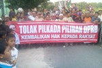 Warga Desa Pilang, Masaran, Sragen, berjalan di jalan desa setempat sembari membentangkan spanduk penolakan pilkada oleh DPRD, Senin (15/9/2014) sore. (Kurniawan/JIBI/Solopos)