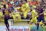 Pemain Villareal Trigueros meloncat berebut bola dengan pemain Barcelona Haddadi. JIBI/Rtr/Heino Kallis