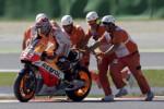 Petugas track mendorong motor Marquez untuk menhidupkan mesin setelah terjatuh. JIBI/Rtr/Max Rossi
