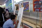 Seorang siswa SLB G Daya Ananda melukis saat pameran hasil karya siswa digelar di Dusun Ganjuran, Desa Widodomartani, Ngemplak, Sleman, Selasa (30/9/2014). (Rima Sekarani/JIBI/Harian Jogja)
