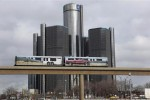 Two cars of the public rail are seen covered with a advertisement for 2014 Chevy Silverado pickup truck as they move past General Motors World Headquarters in Detroit (Reuters)