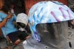 Pemilik usaha jasa cat helm, Bambang Prasetyo, 28, menyelesaikan pewarnaan helm di bengkel cat motor di Nusukan, Banjarsari, Solo, Jawa Tengah, Jumat (17/10/2014). Pewarnaan helm dengan teknik graffiti tersebut dikenai tarif Rp45.000-Rp60.000 per helm tergantung tingkat kesulitan gambar. Bambang mengaku mampu mengerjakan dua buah helm dalam satu hari. (Ardiansyah Indra Kumala/JIBI/Solopos)