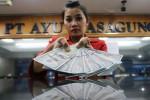 Karyawati PT Ayu Masagung menghitung uang dolar di kantornya, Jakarta, Kamis (23/10/2014). Nilai tukar rupiah terhadap dolar AS kembali melemah pada akhir perdagangan Kamis ini. (Nurul Hidayat/JIBI/Bisnis)