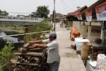 Pedagang kayu dan arang, Joko Warsito, menata kayu di depan kiosnya, di selter pedagang kaki lima (PKL) kawasan Komplang, Banjarsari, Solo, Jawa Tengah, Kamis (16/10/2014). Sejumlah pedagang di selter tersebut mengeluhkan tidak adanya pagar pembatas dengan sungai. Menurut Joko Warsito, salah seorang pelanggannya trauma datang ke kiosnya karena hampir tercebur sungai saat hendak mengambil arang dengan mengendarai sepeda berbronjong. (Ardiansyah Indra Kumala/JIBI/Solopos)