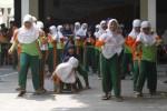 Siswa SD Muhammadiyah 1 Solo mengikuti lomba balap bakiak di sekolah mereka, Kamis (16/10/2014). Perlombaan permainan tradisional tersebut digelar untuk mengisi waktu jeda kegiatan belajar mengajar setelah siswa menempuh ujian tengah semester (UTS). (Septian Ade Mahendra/JIBI/Solopos)