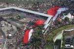 Bendera Merah Putih ukuran raksasa di kibarkan warga disela penyambutan kedatangan Presiden RI Joko Widodo bersama Wakil Presiden RI Jusuf Kalla. selepas pelantikan di gedung MPR/DPR Jakarta, Senin (20/10/2014). (Endang Muctar/JIBI/Bisnis)