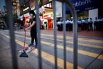 Seorang pengunjuk rasa pro demokrasi menyapu jalan setelah polisi mengambil beberapa barikade di lokasi protes di daerah komersial Causeway Bay di Hong Kong, Selasa (14/10/2014). (JIBI/Solopos/Reuters)