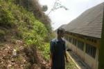 Wakil Kepala SMPN 3 Jatiyoso Bidang Kesiswaan, Warino, menunjukkan lokasi tebing di belakang sekolah setempat, Rabu (22/10/2014). Saat musim hujan, tebing tersebut sering mengalami longsor. (Bayu Jatmiko Adi/JIBI/Solopos)