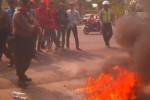 Aparat polisi Sukoharjo tengah memadamkan api yang disulut para pendemo dari mahasiswa Univet Bangun Nusantara serta Universitas Muhammdiyah Surakarta (UMS) Kartasura di depan gapura Univet, Jumat (21/11/2014). Mahasiswa menuntut penolakan kebijakan pemerintah menaikkan harga BBM. (Aries Susanto/JIBI/Solopos)