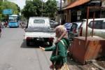 Calon penumpang bus Batik Solo Trans (BST) terpaksa menunggu rapid transit itu di bawah halte portabel yang tersedia di tepian Jl. Veteran, Gading, Solo, Jawa Tengah, Minggu (16/11/2014). Akses calon penumpang itu ke halte tertutup mobil yang parkir sembarangan. (Septian Ade Mahendra/JIBI/Solopos)