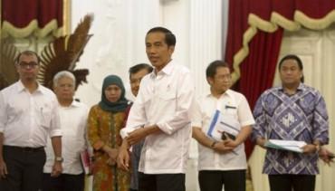 """Presiden Joko Widodo (tengah) menggulung lengan kemeja saat didampingi Wapres Jusuf Kalla (keempat dari kiri) dan para menteri Kabinet Kerja bergegas meninggalkan ruangan konferensi pers seusai mengumumkan kenaikan harga bahan bakar minyak (BBM) bersubsidi di kompleks Istana Kepresidenan Jakarta, Senin (17/11/2014) malam. Presiden Jokowi sebelumnya mengumumkan harga baru BBM bersubsidi—yang disebutnya sebagai """"harga BBM baru""""—adalah Rp8.500/liter untuk premium dan Rp7.500/liter untuk solar. (JIBI/Solopos/Antara/Andika Wahyu)"""
