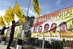 Sejumlah pekerja memasang bendera dan spanduk berlambangkan pohon beringin di pagar pembatas Tol Bali Mandara sebagai persiapan pelaksanaan Musyawarah Nasional (Munas) IX Partai Golkar di Nusa Dua, Badung, Bali, Jumat (28/11/2014). Dewan Pimpinan Daerah (DPD) Partai Golkar Bali memastikan munas partai yang rencananya digelar di Nusa Dua, Minggu (30/11/2014) hingga Kamis (4/12/2014) itu dapat berlangsung dengan aman. (JIBI/Solopos/Antara/Nyoman Budhiana)
