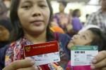 Warga menunjukan Kartu Indonesia Sehat (KIS) dan Kartu Keluarga Sejahtera (KKS) saat peluncuran kartu tersebut oleh Presiden Joko Widodo (Jokowi) di Kantor Pos Besar, Jakarta, Senin (3/11/2014). Peluncuran kartu tersebut ditujukan sebagai jaring pengaman sosial peralihan subsidi bahan bakar minyak. (JIBI/Solopos/Antara/Fanny Octavianus)