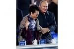 Presiden Putin bantu gunakan selendang ibu negara Tiongkok Peng Liyuan (Reuters)