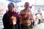 Kedua warga penerima bantuan kompensasi BBM dalam program keluarga sejahtera menunjukkan Kartu Perlindungan Sosial (KPS) dan uang kompensasi yang diterimanya di Kantor Pos Wates, Senin (24/11/2014). (Harian Jogja/Holy Kartika N.S)