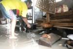 Wasdi, 54, warga Dusun Sanggrahan, Desa Sanggrahan, Kecamatan Grogol, Sukoharjo, berusaha menguras air, luapan Sungai Sanggrahan, yang menggenangi rumahnya, Rabu (17/12/2014). Sementara tetangganya, Darmini, 59, berusaha membersihkan perabotan dapur yang terendam air. (M Khodiq Duhri/JIBI/Solopos)