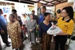 Koordinator Lapangan Artha Graha Peduli Unit Bank Artha Graha Lidya Sinaga memberikan paket sembako murak kepada warga pada Pasar Murah Artha Graha Peduli di wilayah Rawa Badak, Tanjung Priok, Jakarta Utara, Jumat (5/12/2014). Artha Graha Peduli yang bekerja sama dengan Indofood, Kementrian Perdagangan, dan Pramuka Kwartir Daerah Khusus Ibukota Jakarta menggelar pasar murah di lebih dari 1.700 titik di seluruh Indonesia. Paket sembako murah itu didistribusikan kepada warga yang kurang beruntung untuk membantu meringankan beban masyarakat dengan subsidi lebih dari 50 persen dari harga normalnya. (Nurul Hidayat/JIBI/Bisnis)