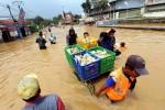 Sukarelawan mendistribusikan makanan dengan menerjang banjir di kawasan Dayeuhkolot, Kabupaten Bandung, Jawa Barat, Senin (22/12/2014). Badan Pengendalian Bencana Daerah (BPBD) mencatat banjir akibat luapan Sungai Citarum itu melanda tiga kecamatan di Kabupaten Bandung dan telah merendam lebih dari 1.600 rumah warga. (Rachman/JIBI/Bisnis)
