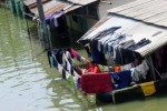 Seorang perempuan warga bertahan di tempat tinggalnya yang terkepung genangan air di Bojongsoang, Kabupaten Bandung, Jawa Barat, Minggu (21/12/2014). Menurut Badan Penanggulangan Bencana Daerah (BPBD) Kabupaten Bandung, total pengungsi akibat banjir yang melanda kawasan Bandung Selatan selama beberapa hari terakhir ini telah mencapai 4.940 jiwa. Mereka adalah warga tujuh kecamatan yang terendam banjir akibat luapan Sungai Citarum. (JIBI/Solopos/Antara/Novrian Arbi)