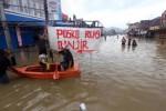Warga kawasan niaga Dayeuhkolot, Kabupaten Bandung, Jawa Barat tetap beraktivitas di tengah genangan air yang meluap dari Sungai Citarum, Rabu (24/12/2014). Bahkan banjir posko banjir pun didirikan di tengah genangan air tersebut. Banjir yang melanda Bandung Selatan selama sepekan terakhir ini telah melumpuhkan aktivitas niaga atau perekonomian di kawasan yang diterjang banjir Bandung itu. (Rachman/JIBI/Bisnis)