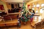 Jemaat menghias pohon Natal di dalam gereja yang terendam banjir di kawasan Dayeuhkolot, Kabupaten Bandung, Jawa Barat, Rabu (24/12/2014). Sedikitnya dua gereja di Dayeuhkolot terendam banjir, meski begitu misa Natal tetap digelar secara sederhana, lantaran akses lokasi gereja terkepung genangan air dari luapan Sungai Citarum. (Rachman/JIBI/Bisnis)