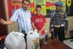 Tersangka Gunawan (tengah) yang juga penjual miras oplosan yang menimbulkan korban jiwa usai diperiksa di ruang Reskrim Polres Sleman berikut sejumlah barang bukti, Selasa (16/12/2014). (JIBI/Harian Jogja/Sunartono)