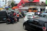 Seorang petugas Dishubkominfo Solo berdiri mengatur kemacetan lalu lintas di simpang empat Ketandan, Purwodiningratan, Solo, Sabtu (27/12/2014). (Tri Rahayu/JIBI/Solopos)