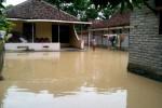 Mukiyem, 70, berjalan di halaman rumahnya yang terencam banjir luapan drainase di Songgorunggi RT 001/RW 006, Kepuh, Nguter, Sukoharjo, Rabu (17/12/2014). (Rudi Hartono/JIBI/Solopos)