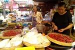 Seorang pedagang di Pasar Wates sedang memilah cabai busuk, sudah beberapa hari ini pedagang tak menambah stok cabai karena tingginya harga cabai merah, Kamis (18/12/2014). (JIBI/Harian Jogja/Holy Kartina N.S.)