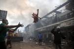 Para pemilik kios di bantu para pegawai, pedagang kaki lima, dan warga mengevakuasi barang-barang dagangan tersisa dari kios-kios Pasar Klewer bagian barat yang terbakar, Minggu (28/12/2014).