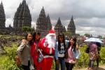 Sejumlah wisatawan di Candi Prambanan berfoto bersama badut berkostum Santa Claus, Jumat (26/12/2014). (Harian Jogja/Rima Sekarani I.N.)
