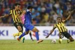 Pemain Thailand Kroekrit Thawikan dihadang pemain Malaysia saat menciptakan gol. JIBI/Rtr/Damir Sago