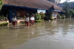 Siswa SDN 1 Prambanan melewati genangan air di halaman sekolahnya, Senin (13/1). Halaman sekolah dan sejumlah ruang kelas di sekolah itu tergenang air akibat hujan deras yang mengguyur wilayah Klaten, Senin (12/1/2015). (Ayu Abriani/JIBI/Solopos)