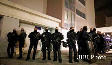 Polisi Prancis, Kamis (8/1/2015) dini hari, berjaga-jaga di akses permukiman warga Paris seusai insiden penyerangan kantor redakai Charlie Hebdo. (JIBI/Solopos/Reuters//Jacky Naegelen)