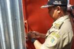Salah satu petugas Satpol PP menggembok pintu masuk pabrik garmen PT Syobal Grace Abadi (SGA) di Desa Kalikotes, Kecamatan Kalikotes, Kamis (29/1/2015). Penggembokan itu agar operasional perusahaan pabrik berhenti total. (Ayu Abriyani K.P/JIBI/Solopos)