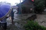 Warga melihat lokasi longsor di anak Kali Dengkeng di kompleks Pasar Kepoh, Desa Kreten, Kecamatan Gantiwarno, Minggu (18/1/2015) petang. Akibat kejadian itu, empat rumah toko (ruko) yang berada di tepi sungai terancam hanyut. (Istimewa)