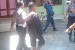 Seorang pemuda, Edo, 22, digelandang aparat polisi setelah ketahuan bercumbu dengan siswi SMP kelas IX di salah satu hotel di Kota Madiun. (JIBI/Solopos/Aries Susanto)