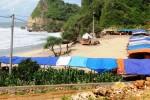 Lapak-lapak pedagang masih terlihat berjejer di pinggir Pantai Nguyahan. Rencananya, seluruh pedagang akan dipindah ke kios yang sedang dibangun, dan lapak-lapak itu akan dibongkar. Foto diambil Jumat (9/1/2015). (JIBI/Harian Jogja/David Kurniawan)